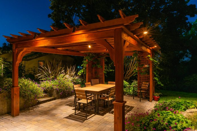 A covered seating area with lights and an awning.