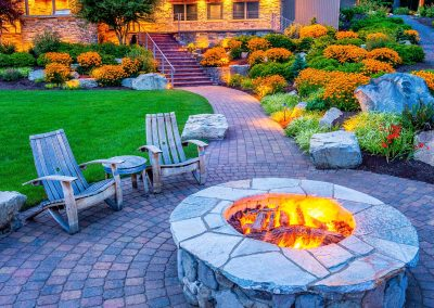 An outdoor fire pit with chairs around it.