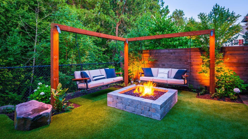 An outdoor seating area with swing chairs and a fire pit.